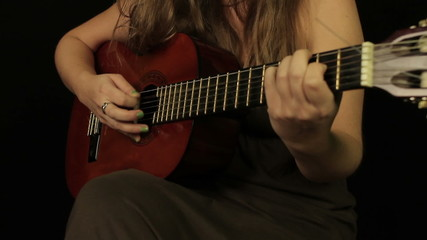 Female hands playing the guitar