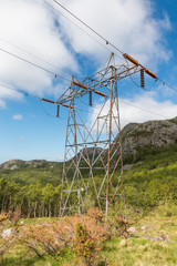 Transmission tower leading up a rocky hill