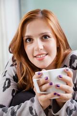 Female Drinking Coffee On Sofa