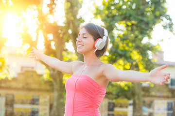 Carefree Girl with Headphones Listening Music at Park