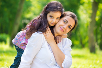 Pretty mother with daughter at summer park
