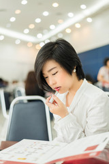 Cute Thai (Asian) businesswoman is wearing lipstick in the offic