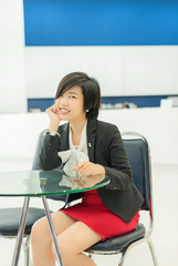 Cute Thai businesswoman sitting and smiling in the office