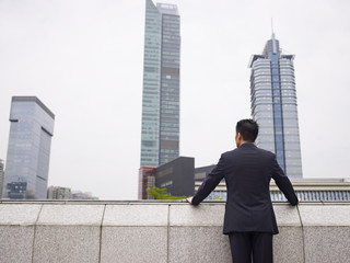 asian business executive looking at the city