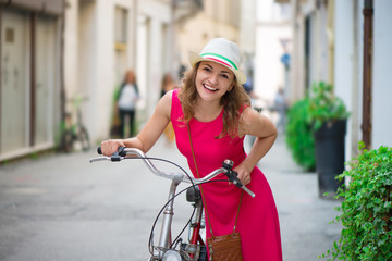 Preaty girl in hat and pink dress riding a bicycle