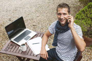 Young man working talking with smart phone in outdoors.