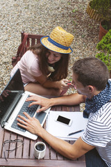 Young couple working with laptop in outdoors.