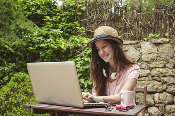 Young woman with straw hat working with laptop in outdoors.