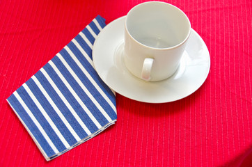 empty white coffee cup on red tablecloth