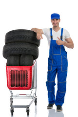 mechanic with tires giving a thumbs up