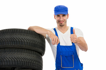 mechanic with tyre giving a thumbs up