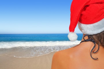 Woman on the beach in santas hat