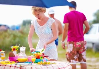 woman preparing picnic table in summer park