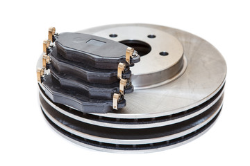 Two metallic brake disks and pads isolated on white background