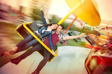 Young happy couple having fun at amusement park
