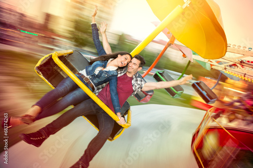 Young happy couple having fun at amusement park - 68374263