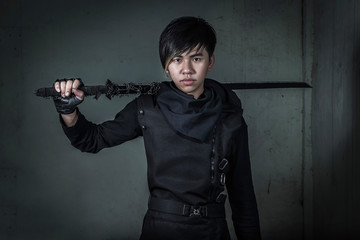 Asian man dresses as Ninja holding sword