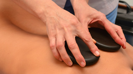 Stone therapy, spa, doctor puts hot stones on the patient's back