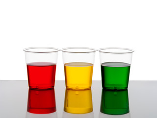 Three plastic cups of drink - red yellow and green.