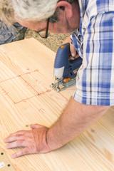 Closeup view of a carpenter building a wooden furniture