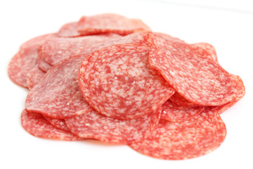 Thin slices of salami in a random pile on white background.