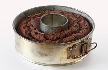 Adjustable round metal baking ring with chocolate sponge cake.
