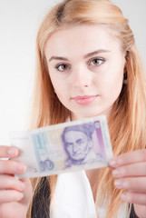 Smiling blond beauty woman holds against banknote