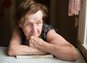 Pensive elderly woman at a table in his house.