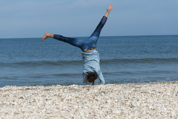 A beautiful energetic young woman doing  gymnastics on beach