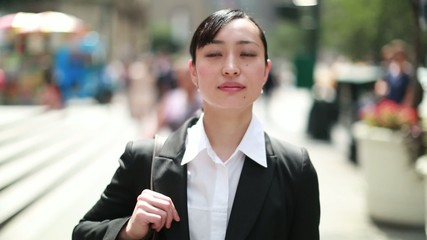 Young Asian business woman in city walking street