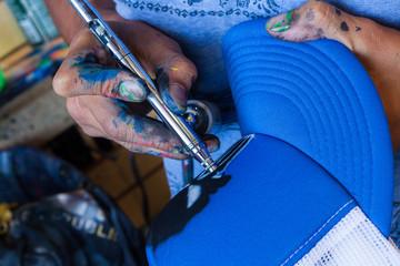 artista che disegna con Aerografo su stoffa