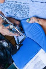 Dettaglio. Artista che disegna con Aerografo su stoffa