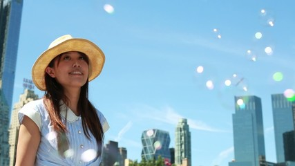 Young Asian woman outdoor in park blowing bubble