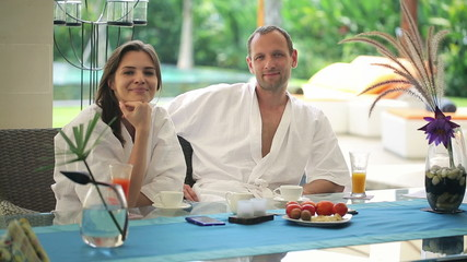 Happy couple chatting by the table in luxury villa