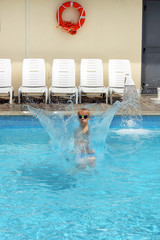 Young boy kid jumping in the pool on vacation