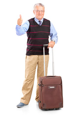Mature man holding a suitcase and giving thumb up