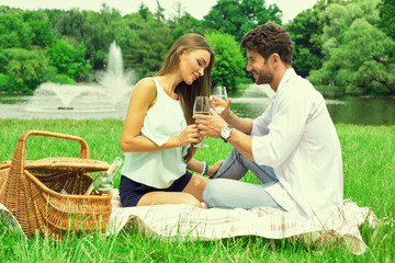 Couple at park having a picnic and drinking white wine