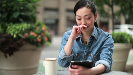 Young Asian woman using tablet pc outdoor