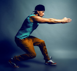 Young handsome male hip-hop dancer in trendy clothing showing so