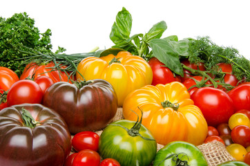 Composition of different varieties of tomatoes and herbs on a bu