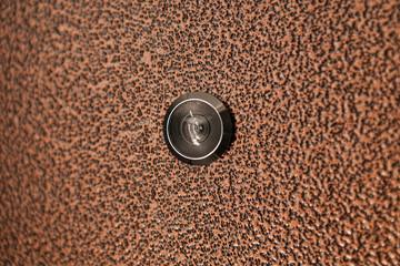 Black peephole in  brown iron door