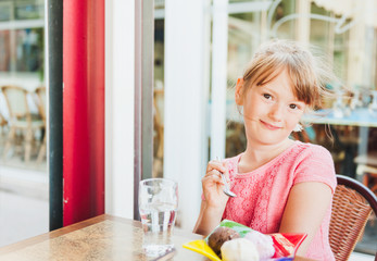 Cute little girl eating ice cream in a cafe