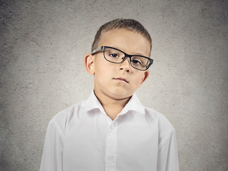 Boy with judgmental face expression on grey wall background