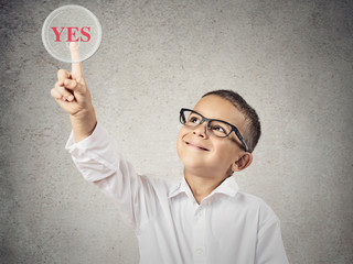 Happy boy touching yes button, grey wall background