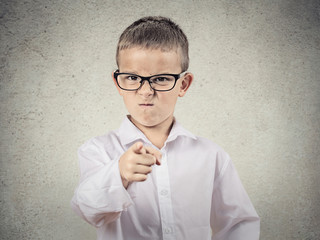 Angry bossy boy pointing finger at someone, grey background