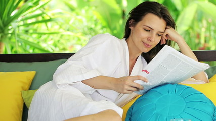 Attractive woman reading magazine, relaxing on gazebo bed