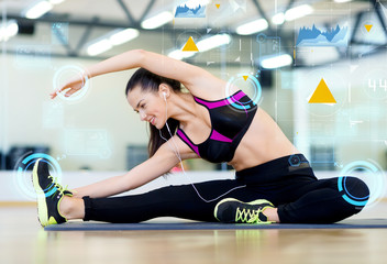 smiling young woman stretching on mat in gym