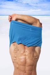 Sexy man undressing on beach.