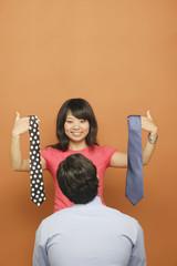 Woman helping man select tie