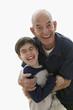 Portrait of grandfather hugging grandson